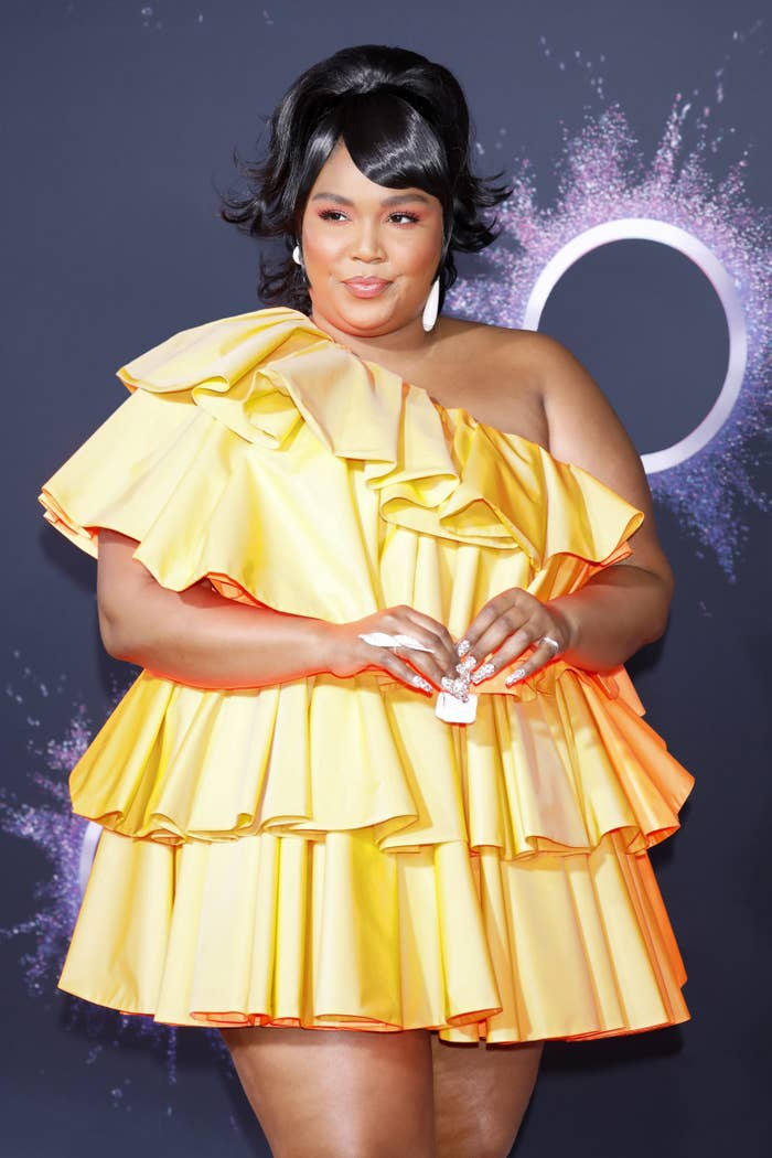 Lizzo in a short tiered dress and holding a tiny purse at a red carpet event