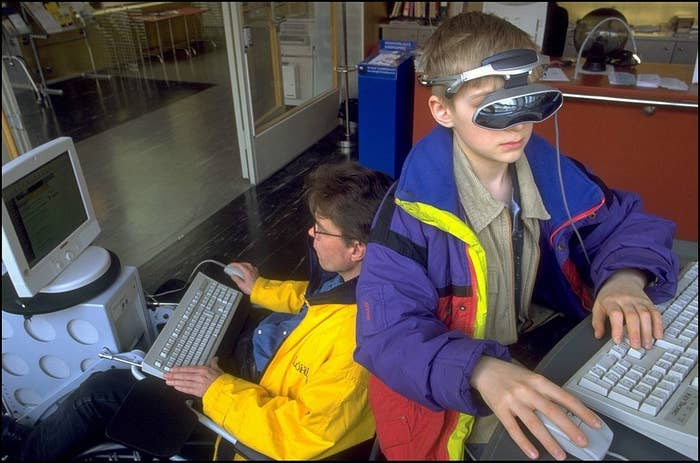 Kid sitting at a computer with a colorful jacket and glasses