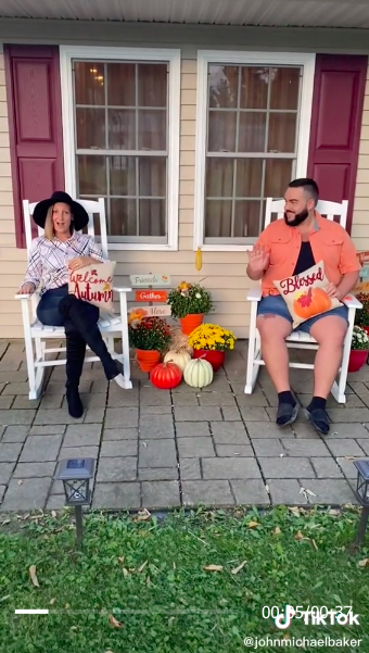 """A woman wearing a large-brimmed hat and sitting on a porch with a """"Welcome autumn"""" pillow in her lap, and a seated man smiling at her and holding a """"Blessed"""" pumpkin pillow in his lap"""