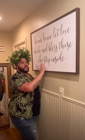 """Wreathed man standing in front of a large framed wall hanging with the saying""""In our home let love abide and bless those who step inside"""""""