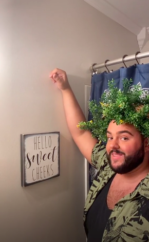 """Smiling wreathed man showing off a framed """"Hello sweet cheeks"""" sign hanging on a wall"""