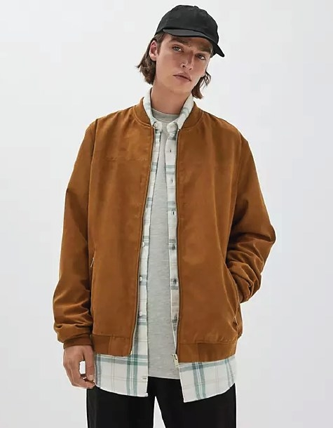 Male model wearing the zip up jacket over a gray t-shirt and flannel