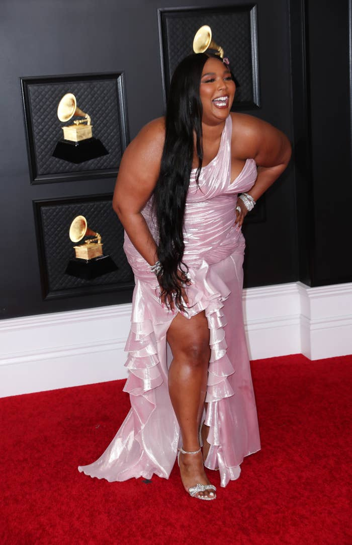 Lizzo laughing as she poses in a one-shoulder ruffled gown on the Grammys red carpet