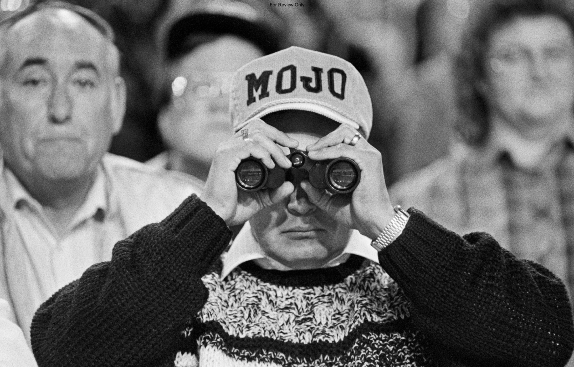 """A person wearing a """"Mojo"""" cap looks through a pair of binoculars"""