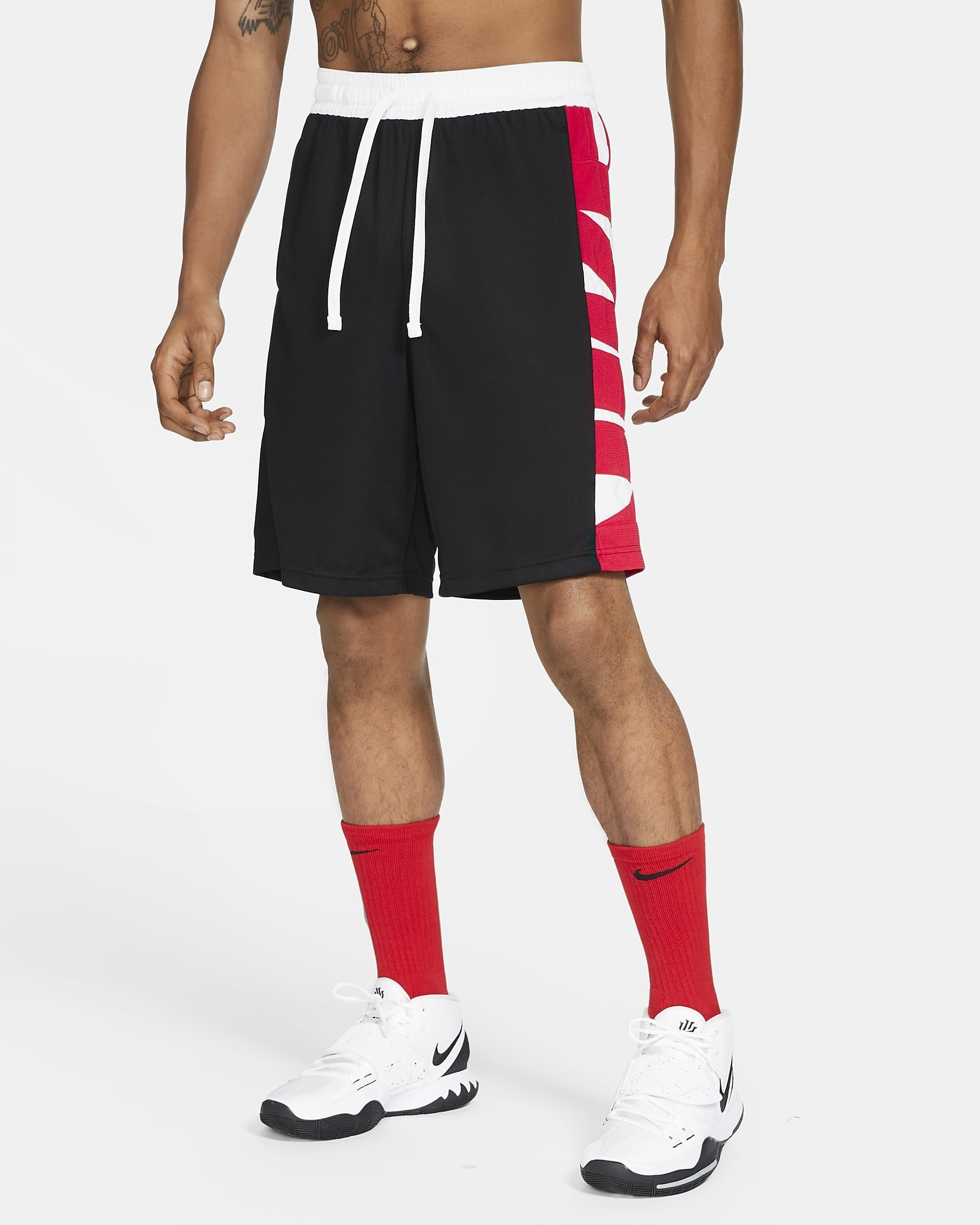 Model wearing black basketball shorts with red strip down the side with white nike logo, worn with red socks and white basketball sneakers