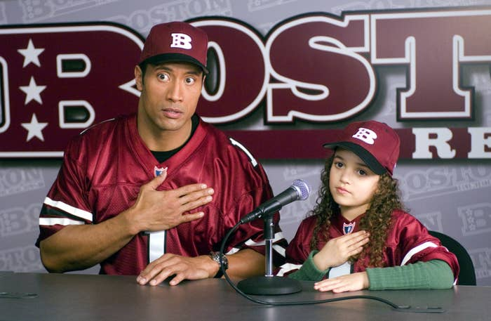 The Rock and young madison at a press conference with their hands over their heards in the game plan