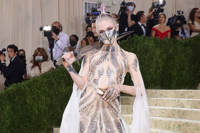 Grimes arriving at the 2021 Met Gala and carrying a sword