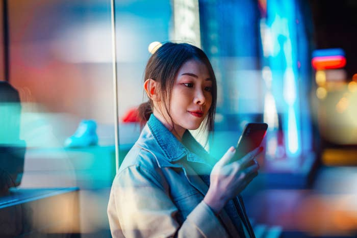 Young woman looking at finances on her phone