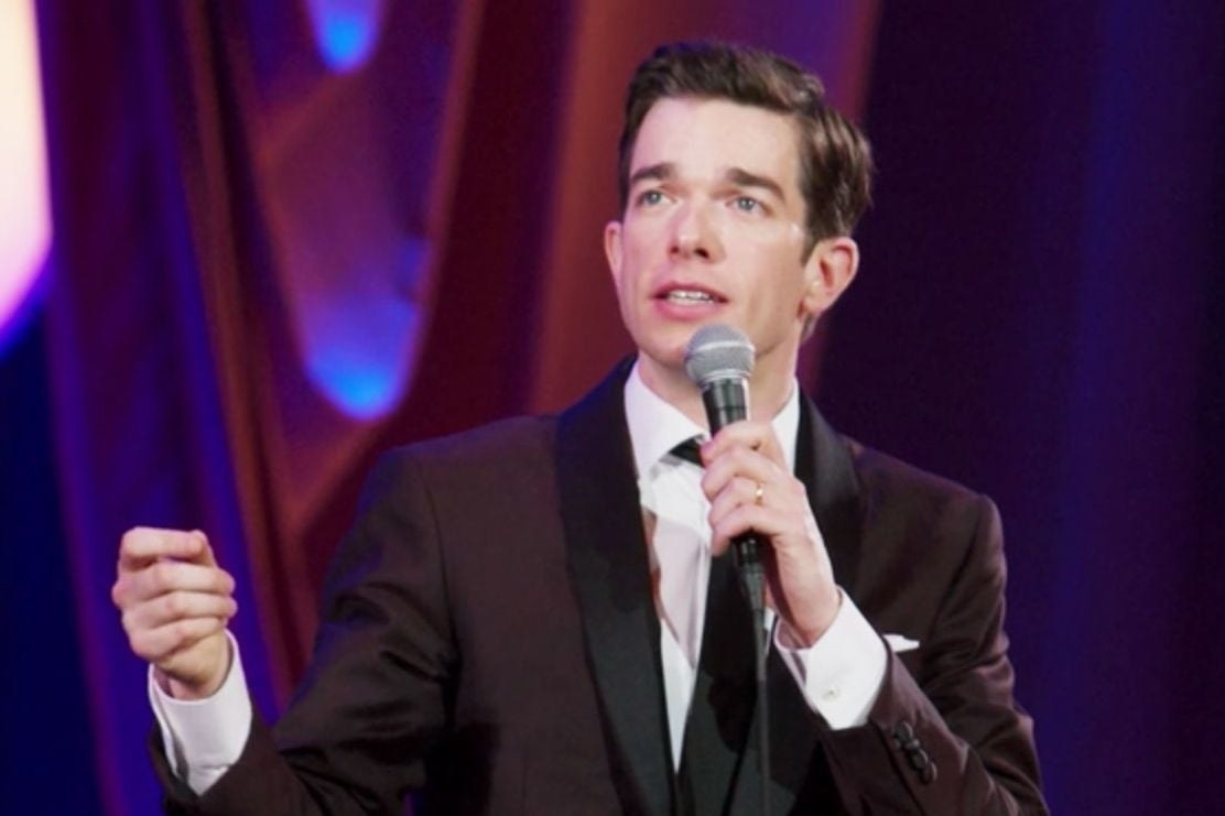 John Mulaney performing stand-up in a dark maroon suit