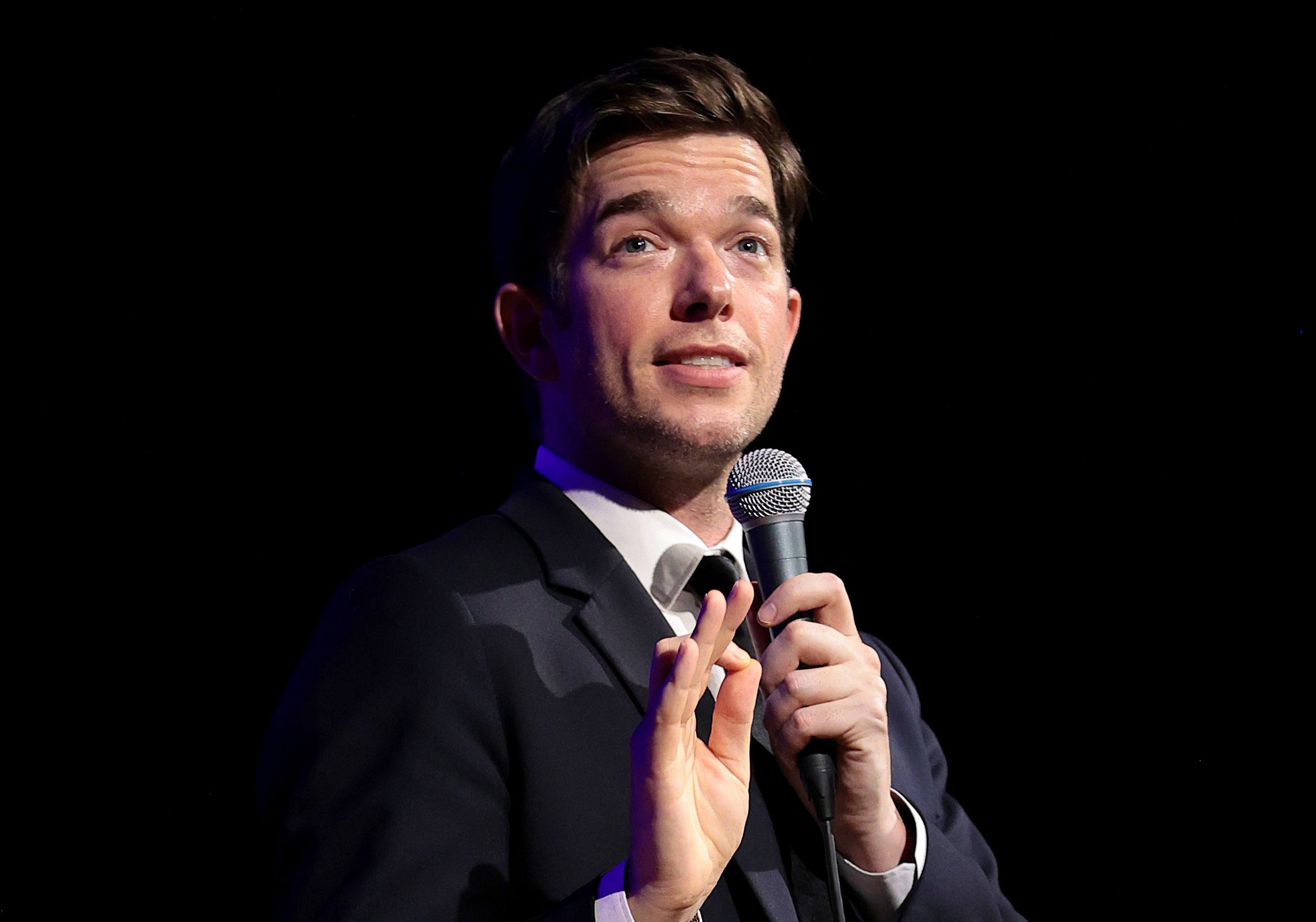 John Mulaney performing stand-up in a gray suit