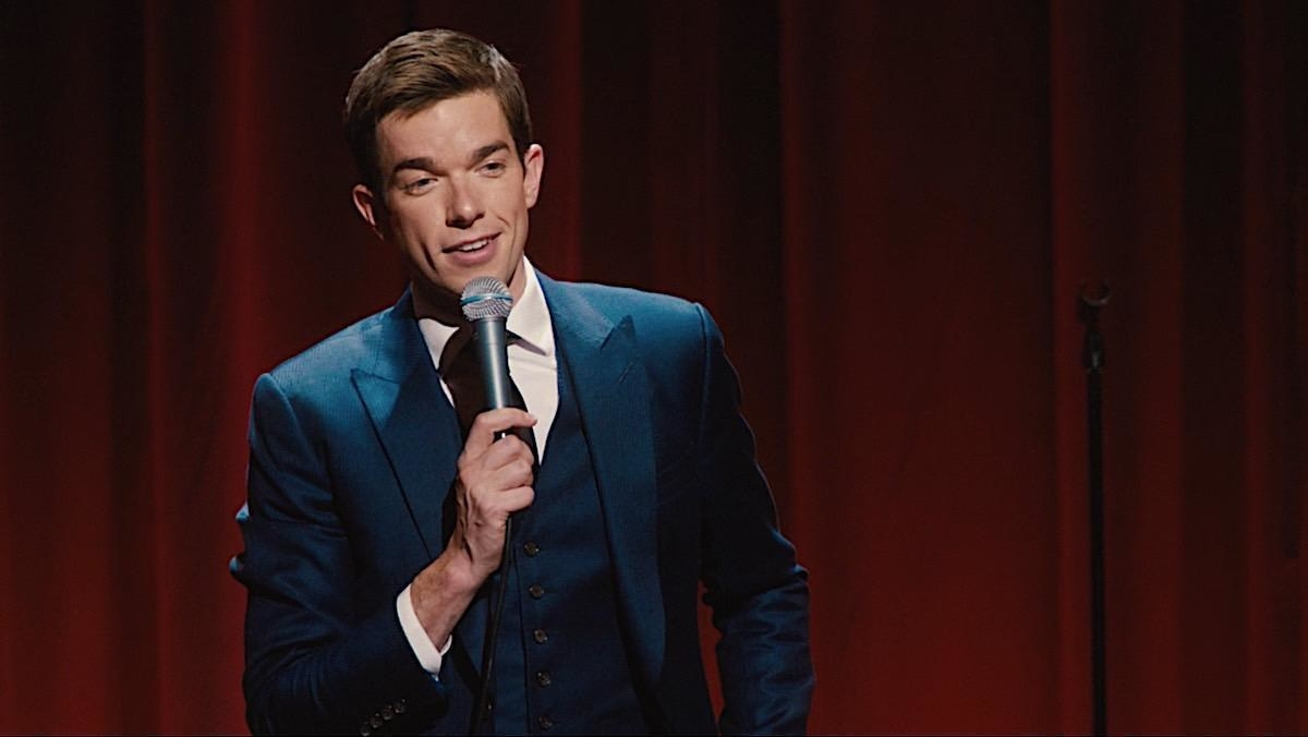 John Mulaney performing standup in a blue suit