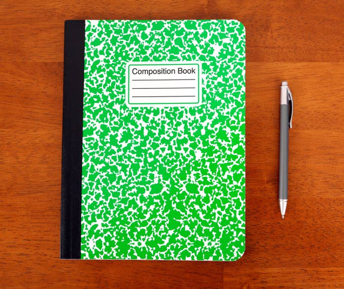 Green composition notebook with a pen next to it