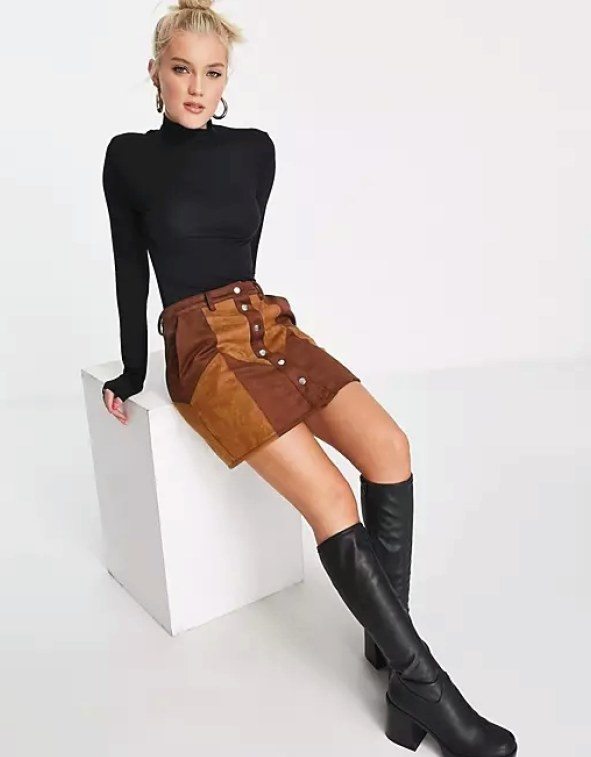 Model wearing the turtleneck with a skirt and boots