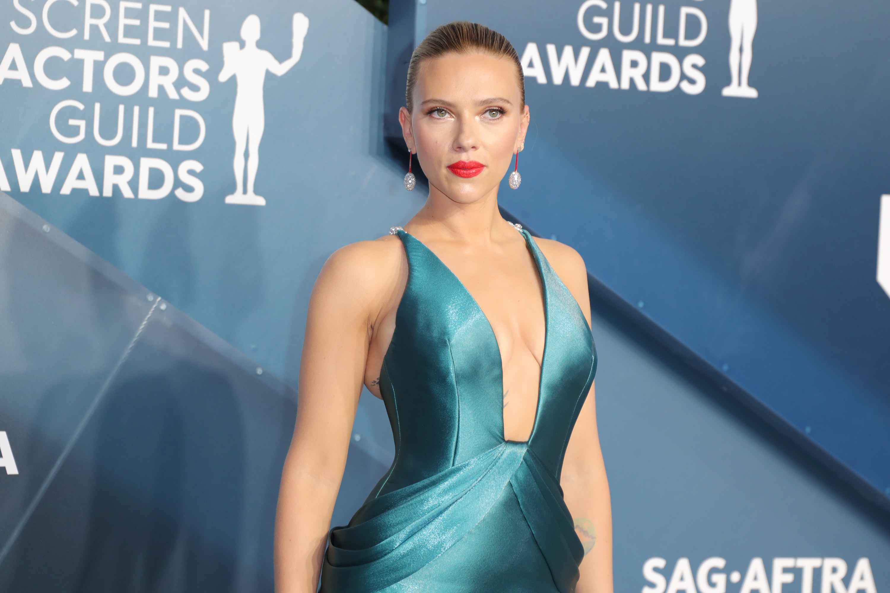 Scarlett wears a teal gown with a plunging square neckline