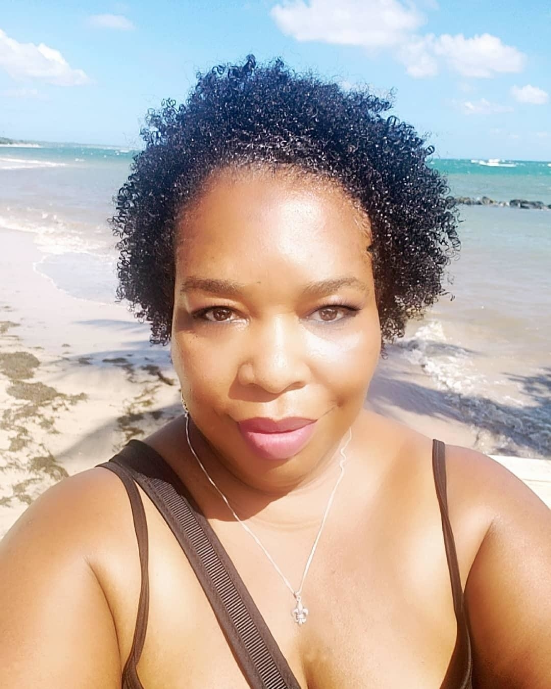 reviewer with natural hair that looks moisturized and defined