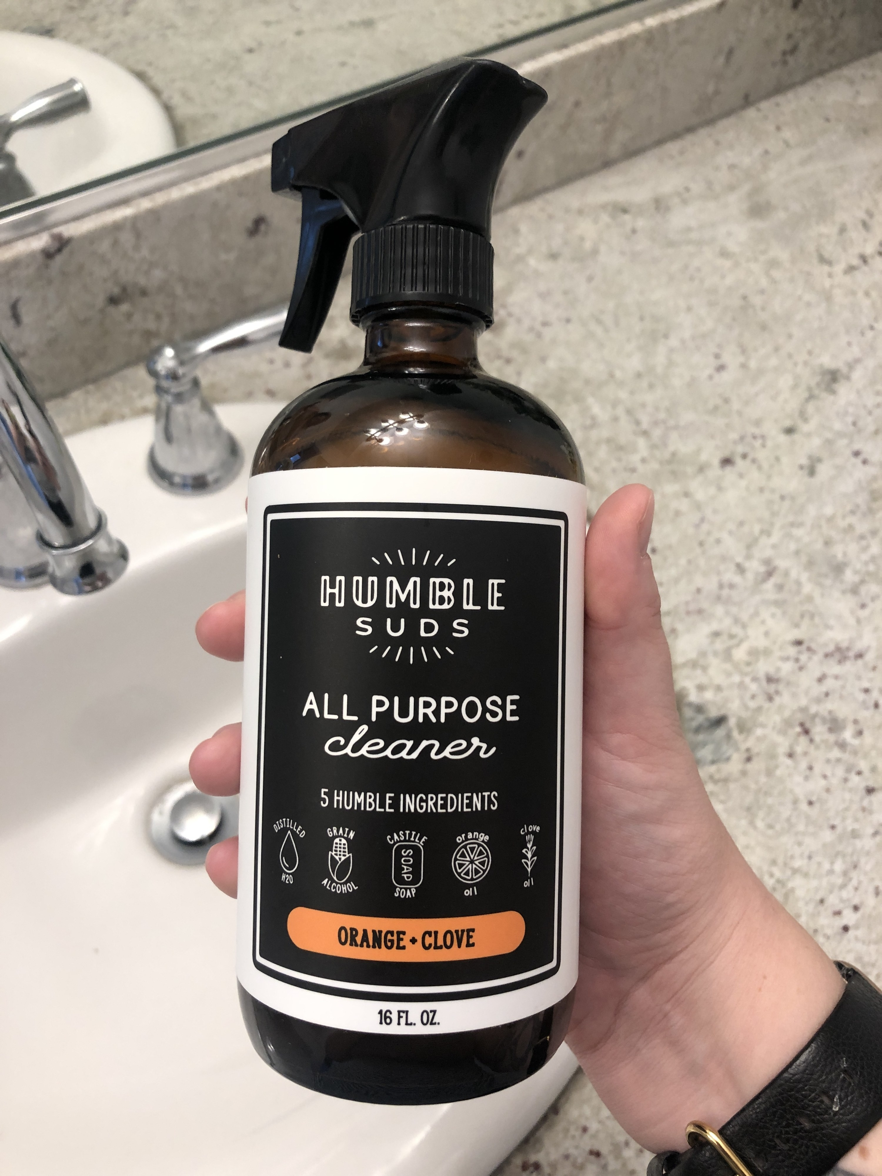 A person holds up the all purpose cleaner in a bathroom