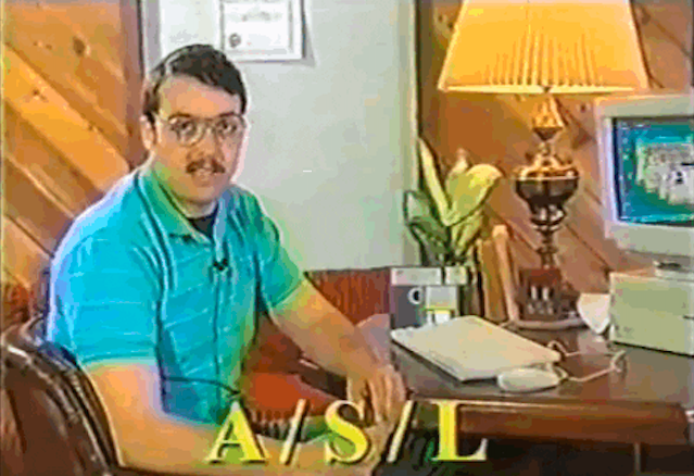 """A man with a mustache sitting in front of a computer with """"A/S/L"""" written on the screen"""
