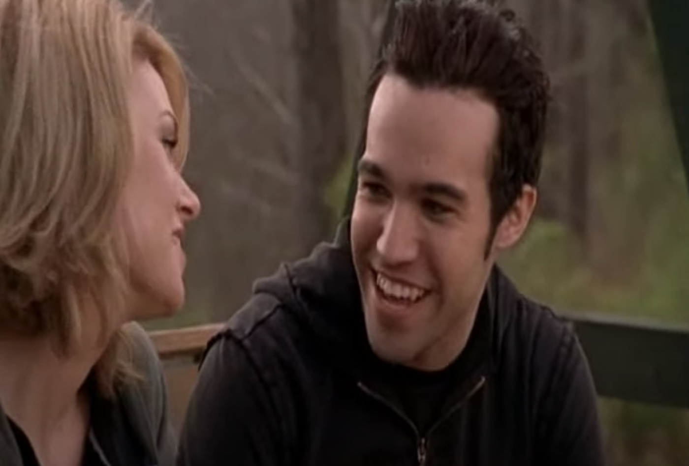 Pete talking to Peyton on a wooden swing bench