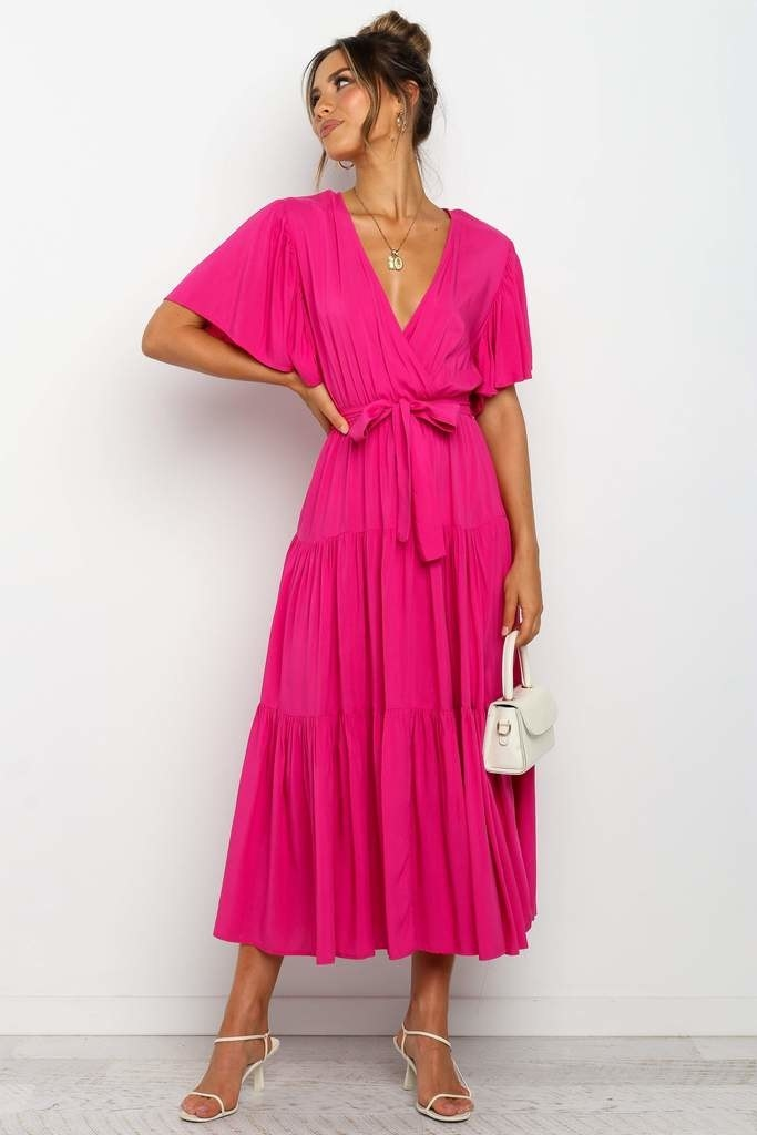 model in bright pink short sleeve tie-waist maxi dress and white sandals