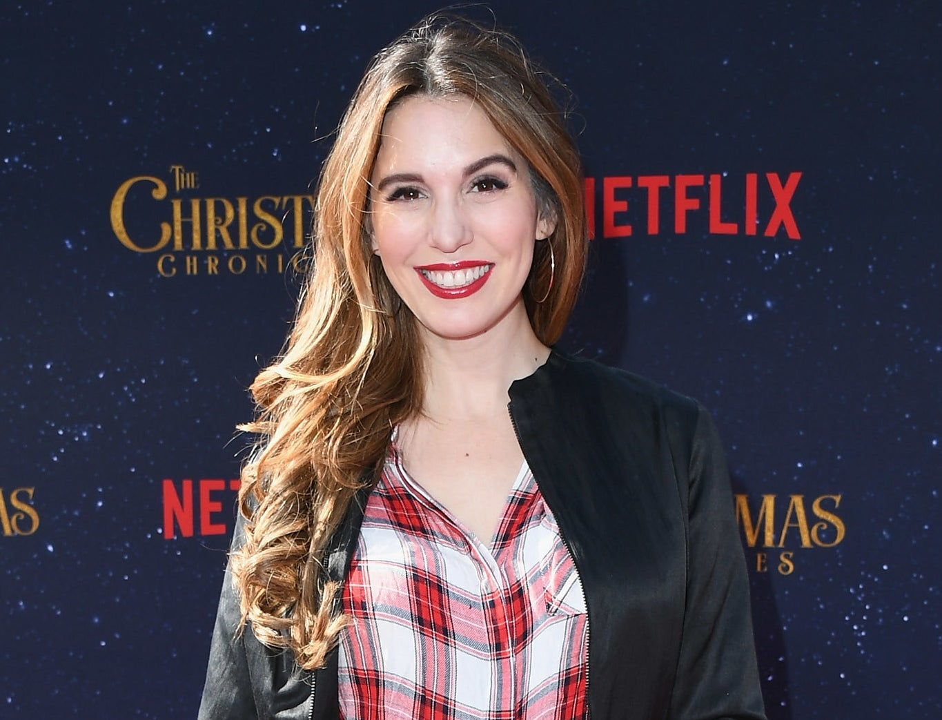 Christy wears a red and white plaid shirt and black jacket