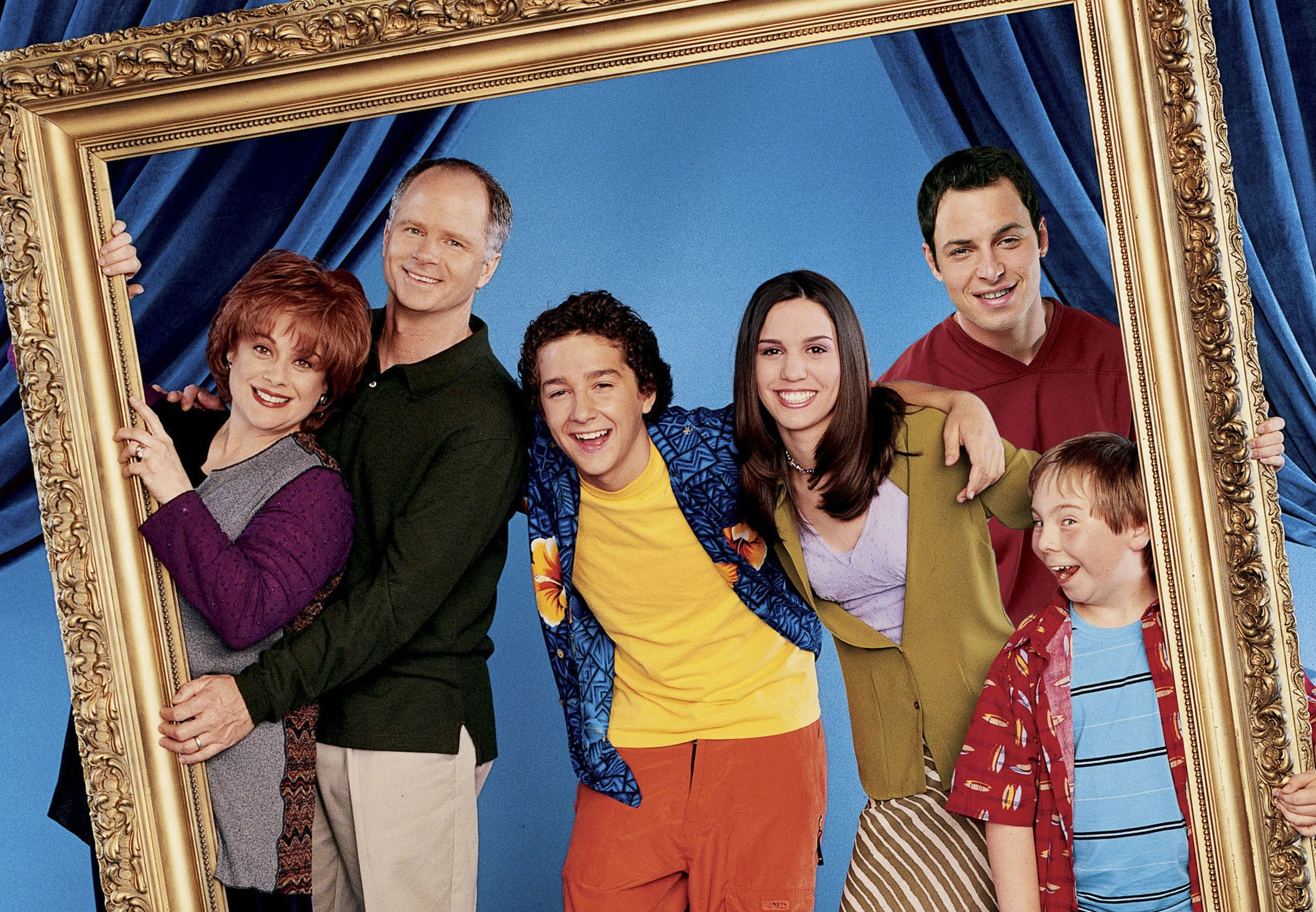 Christy poses with the Even Stevens cast in the middle of a giant frame they are holding up