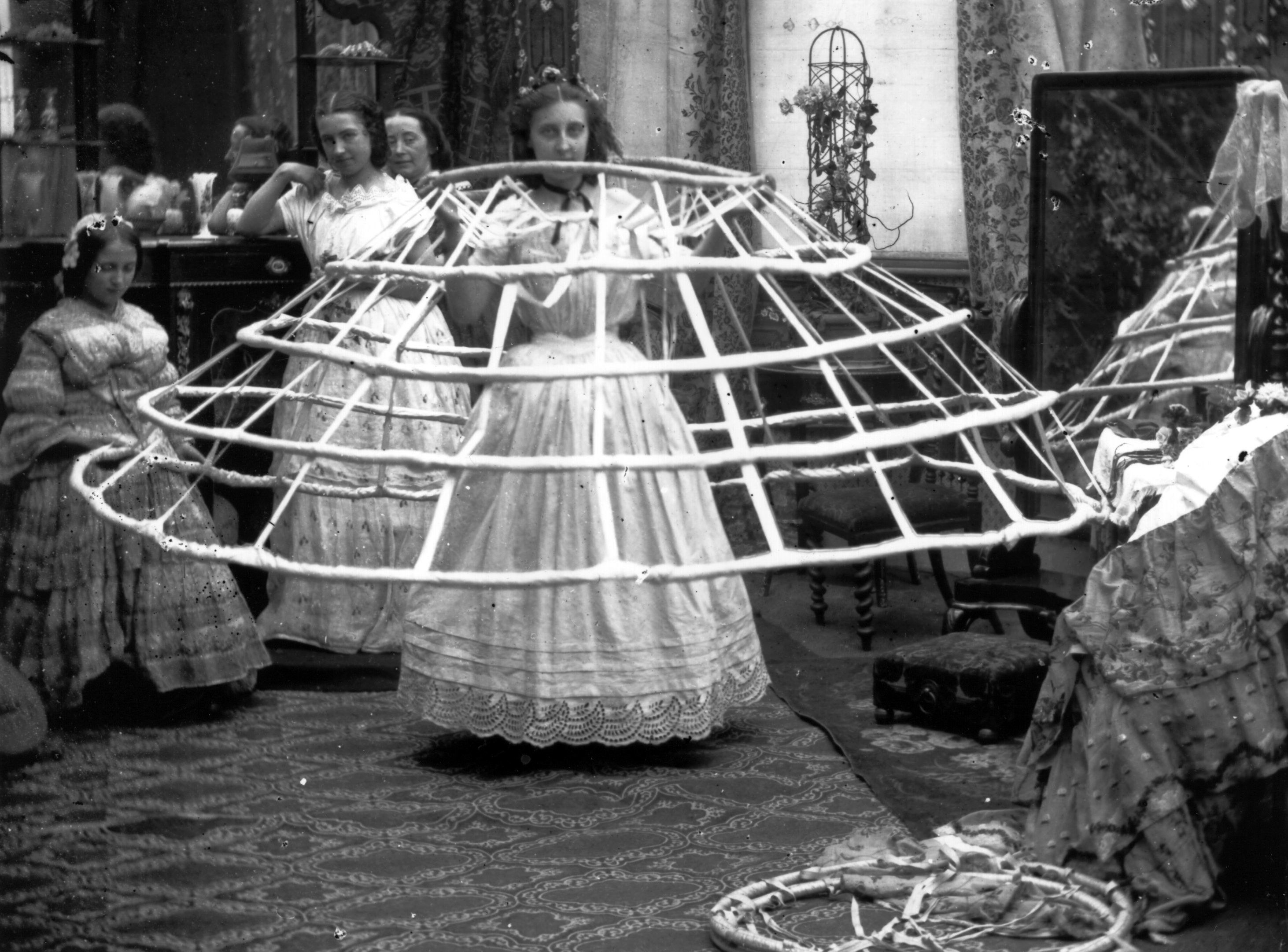 Woman holding up a large hoop skirt, known as acrinoline, that spans her height in width