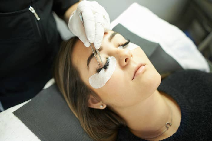 A woman laying down while having her lashes filled in