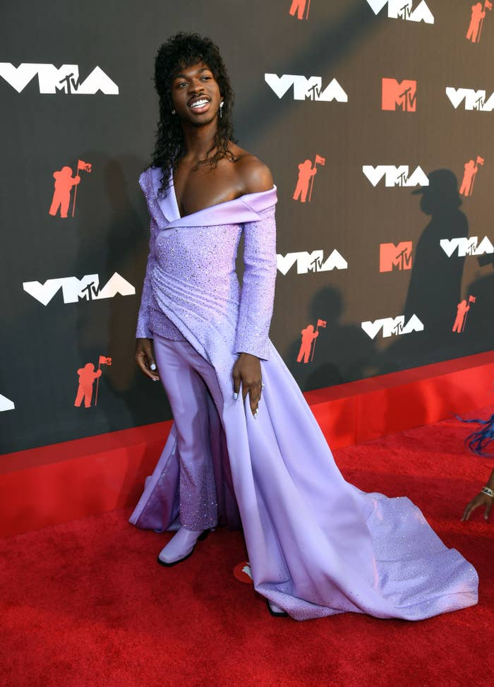 Lil Nas X on the 2021 VMAs red carpet in a suit/dress hybrid outfit and curly wig