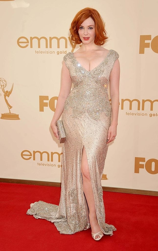Embroidered and jeweled cap-sleeve, V-neck dress with slight shoulder pads, a small train, and a long slit