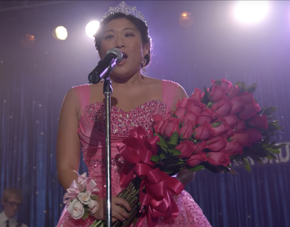 Tina holding roses and speaking at the microphone in the pink dress