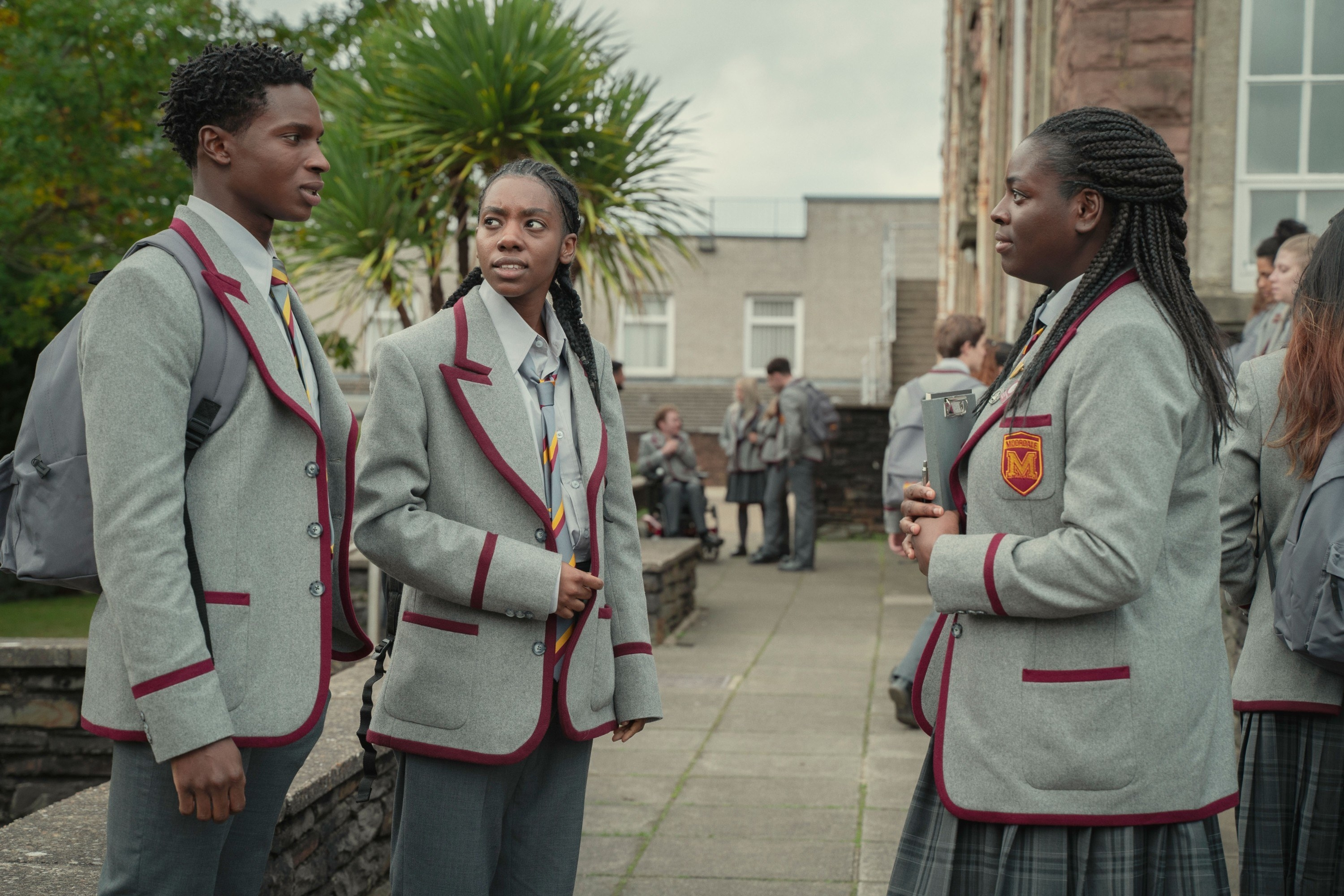 students in long grey blazers with red liner