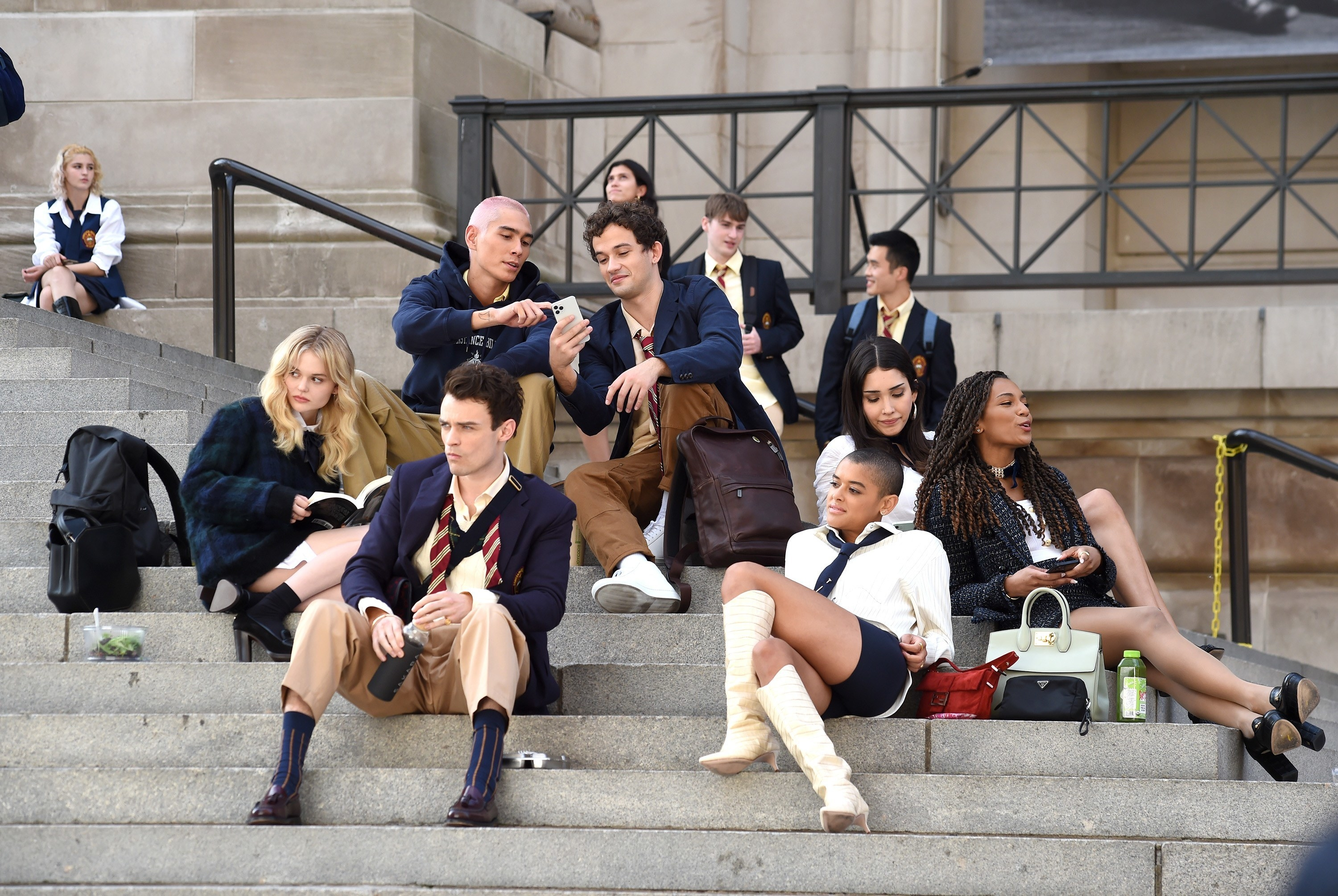 """Aki, Julian, Luna, Monet, Max, Obie, and Audrey from the """"Gossip Girl"""" reboot sitting on the MET stairs"""