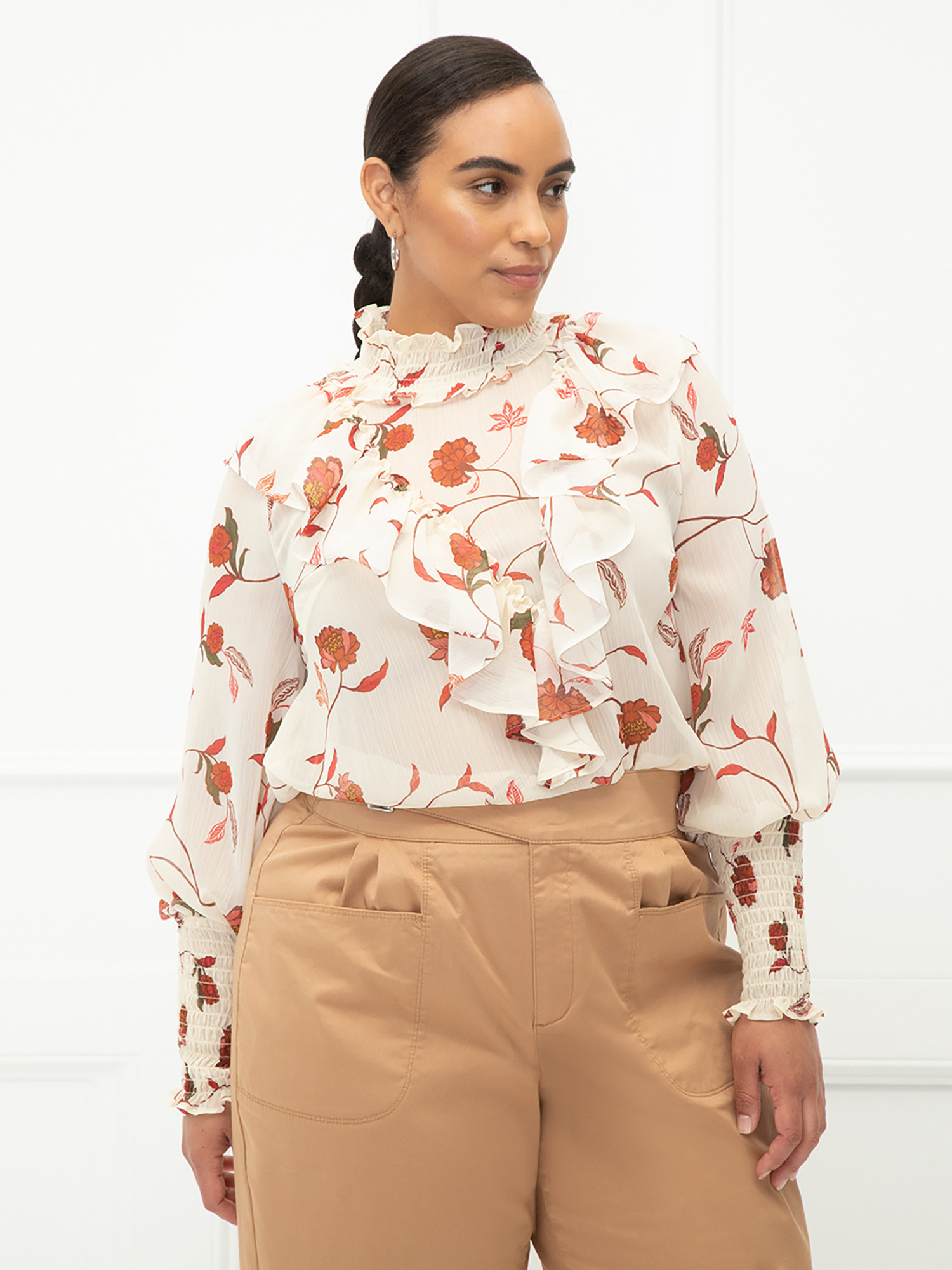 model wearing the long-sleeve ruffle top in cream with red flowers on it