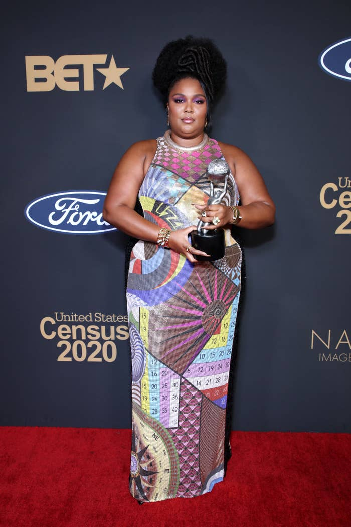 Lizzo posing with her NAACP Image award on the red carpet