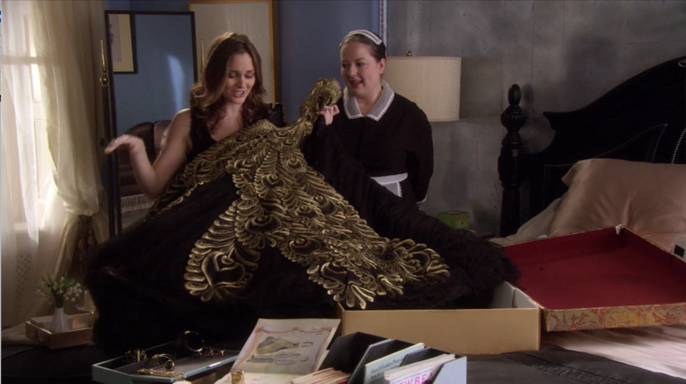 Blair unfolding the dress from a box while her maid watches