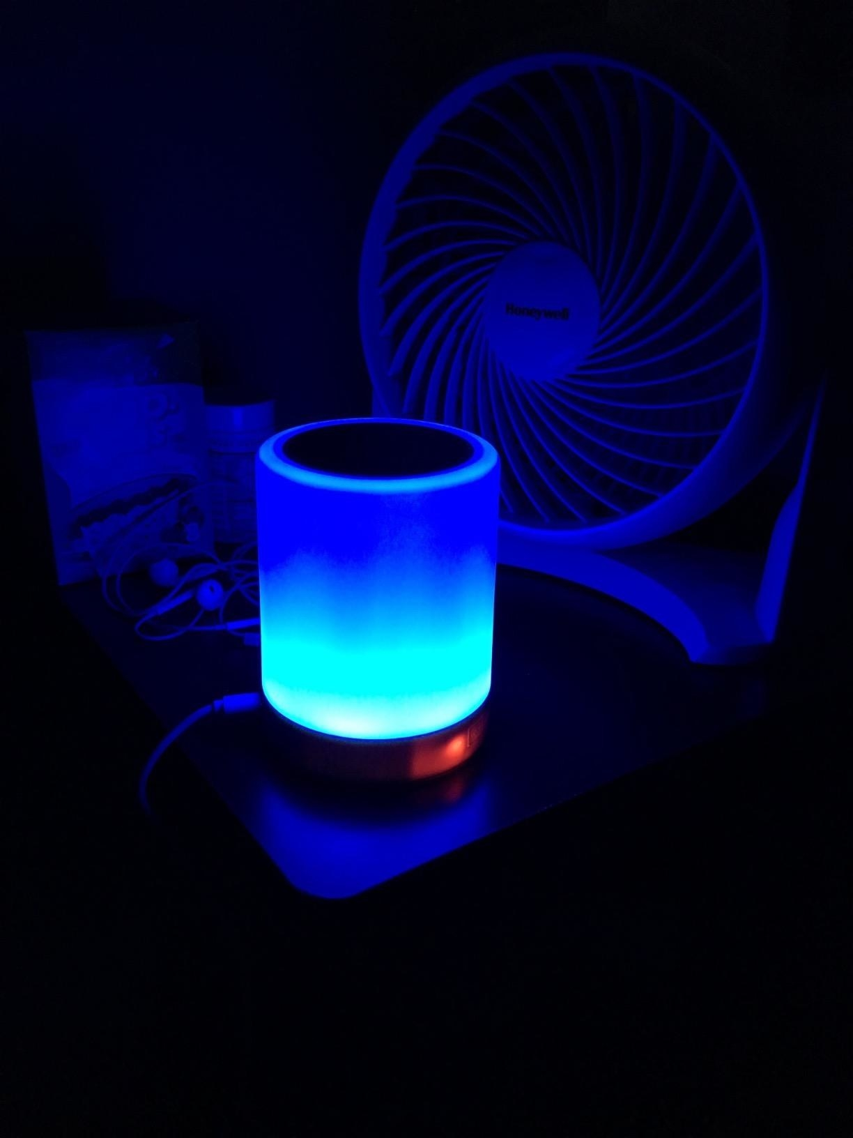 A reviewer's speaker glowing blue
