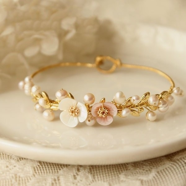 The gold bracelet with pearls and two blossoms