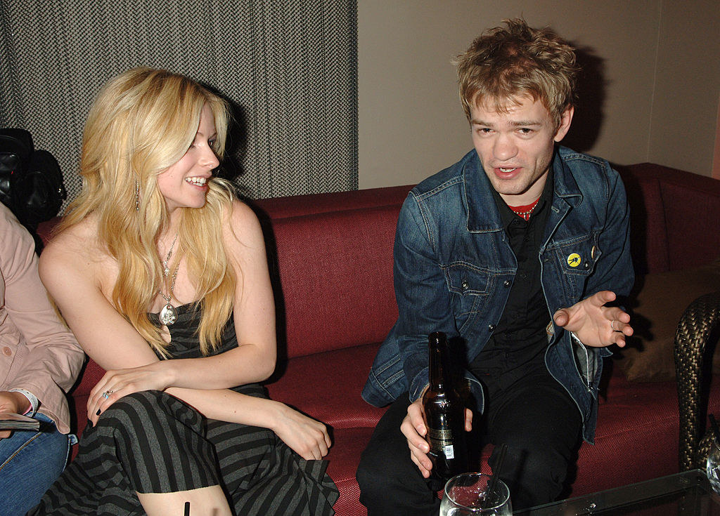at a party and he has a beer and she has a smile