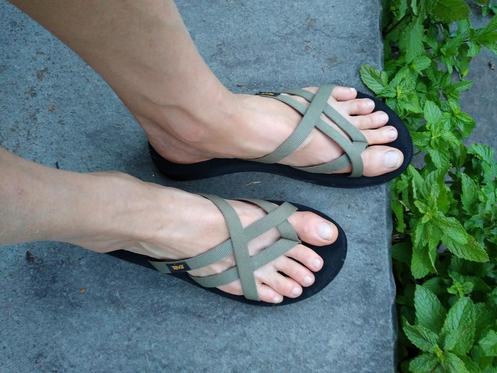 reviewer wearing the flipflops, which have a black footbed and sage green crisscrossing straps