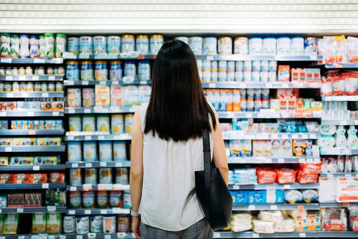 A person standing in front of the refrigerated section of a grocery store