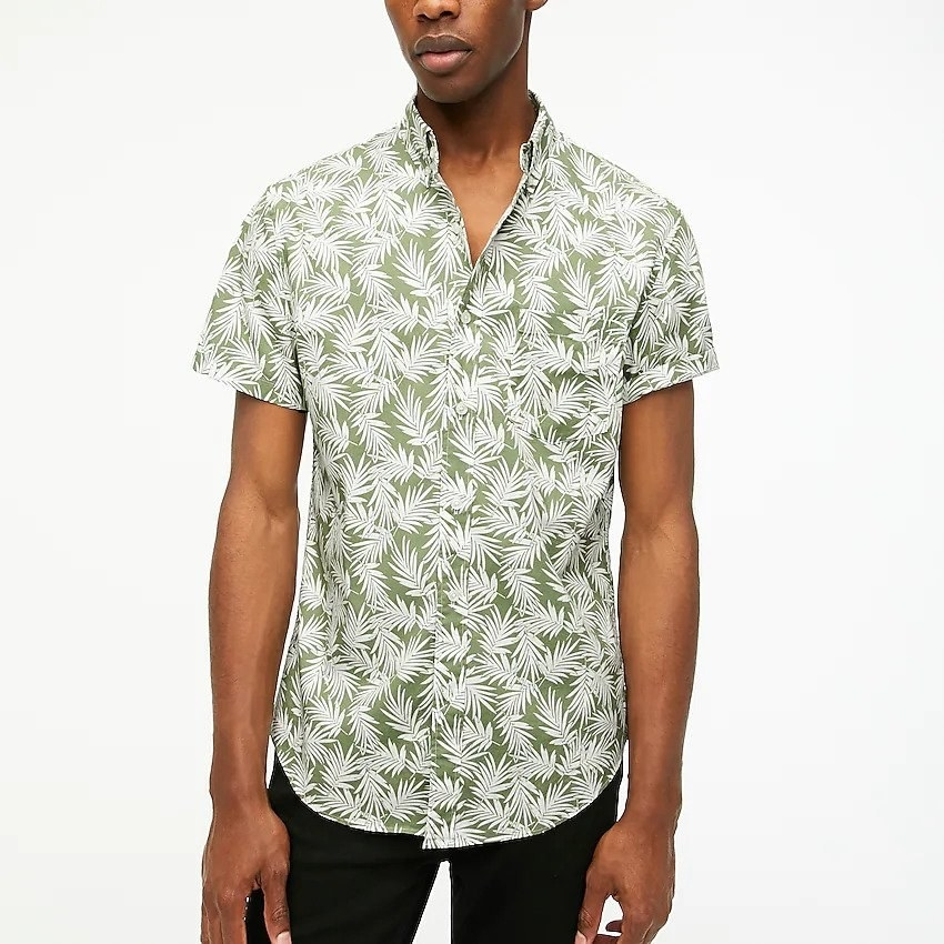 model in short sleeve green button down shirt with white leaf print