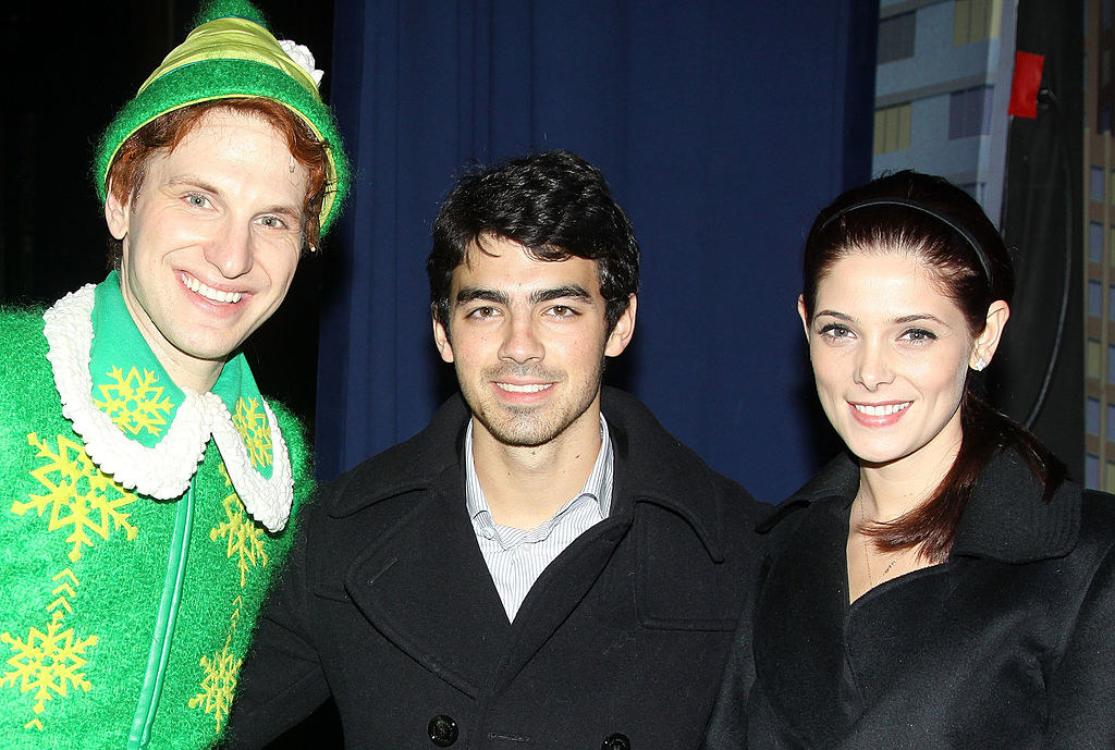 they are posing with a man dressed up as an elf