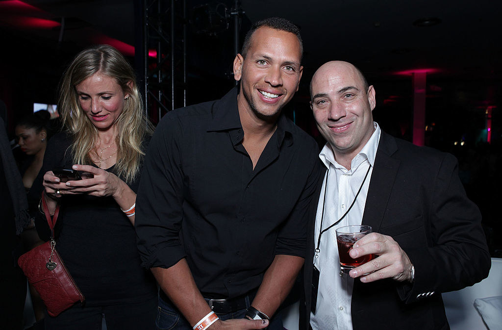 a-rod is posing with a man and cameron is in the background texting