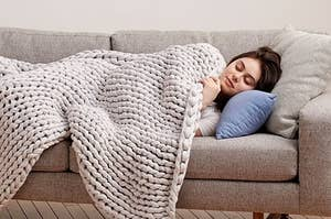 Model taking a couch nap under the grey cable-knit weighted blanket