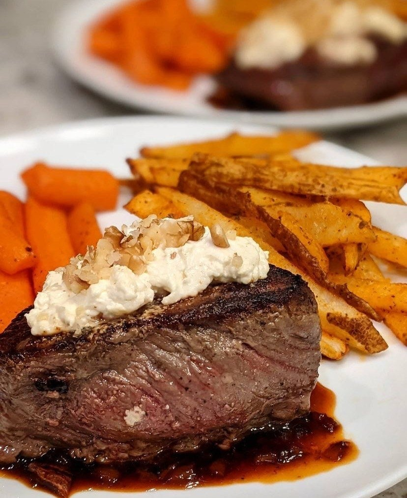 A picture of steak with french fries and carrots