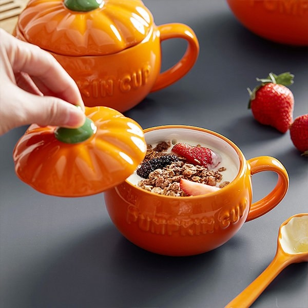 A yogurt parfait in the orange pumpkin bowl with a handle and matching top