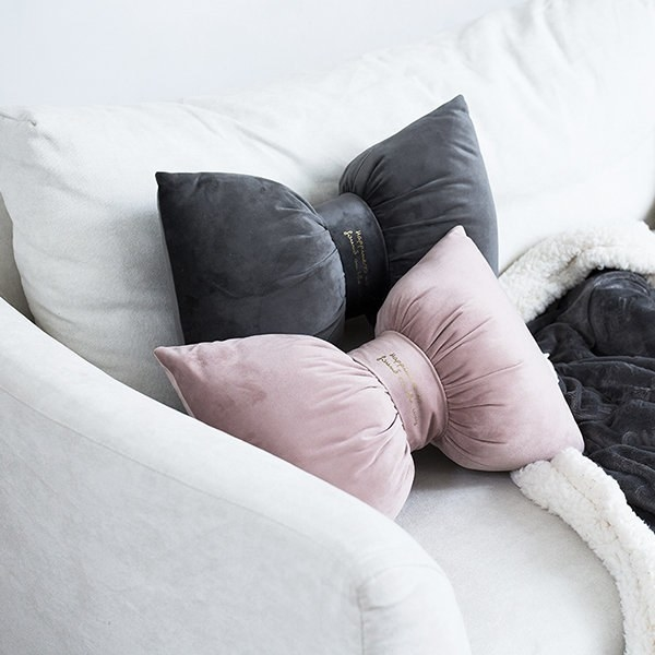 Two of the velvet bow pillows on a couch