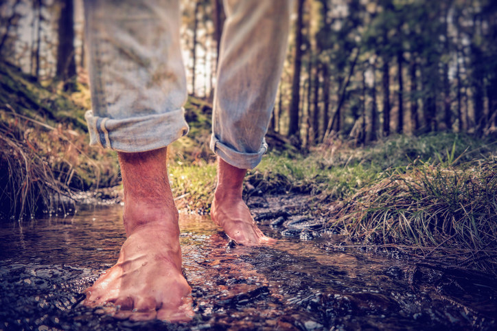 Image of man walking barefoot in a tiny pool of water and dirt