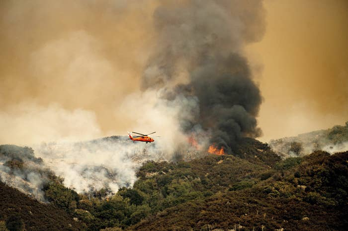 A helicopter flies over a forest fire