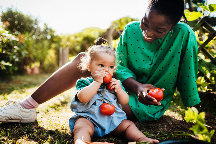 A woman and a child sitting on the ground with fresh tomatoes